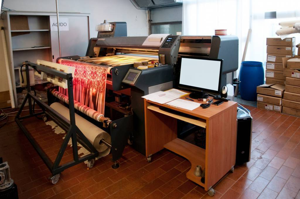 A roll-fed flatbed direct to garment printing creates small batches of highly customized textiles.
