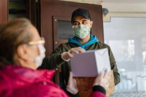 masked man delivering package during coronavirus pandemic