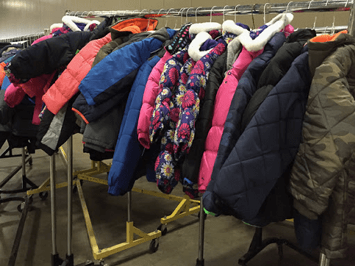 Many donated coats hanging on a rack
