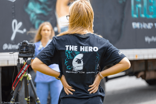 A volunteer wearing a shirt that says The hero behind the mask