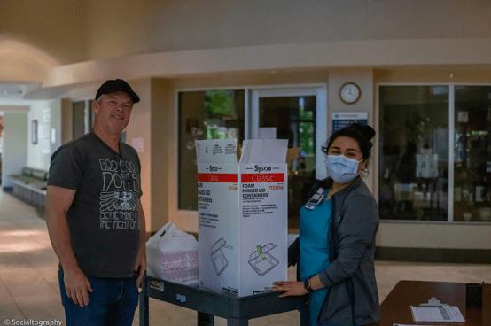 Two volunteers packaging meals